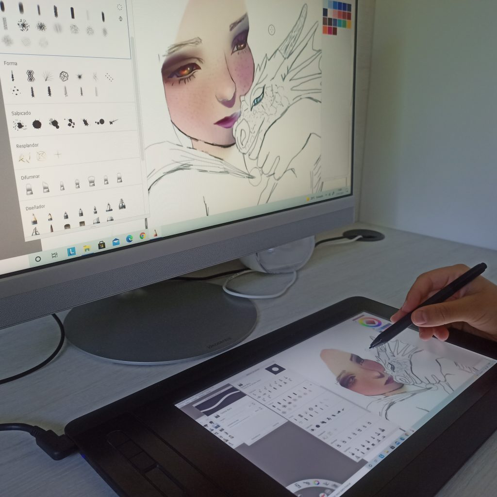 Tableta gráfica con pantalla con un dibujo y ordenador con el mismo dibujo